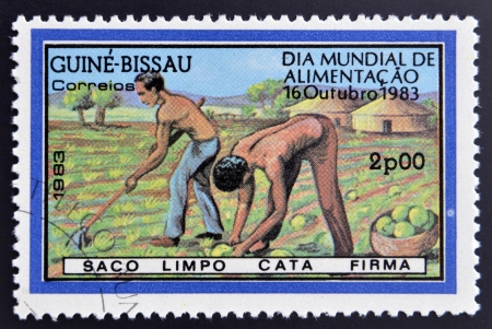 GUINEA BISSAU - CIRCA 1983: a stamp printed in the Republic of Guinea-Bissau commemorative the world food day, showing farmers plowing the land, circa 1983.