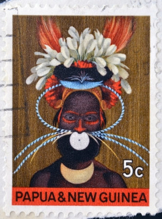 franked: PAPUA NEW GUINEA - CIRCA 1977: stamp printed in Papua New Guinea shows a man in a feathered headdress, circa 1977