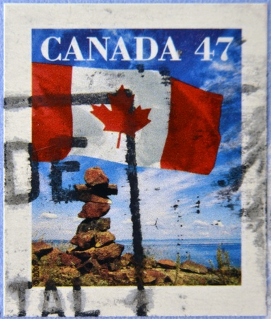 inukshuk: CANADA - CIRCA 2000: A stamp printed in Canada shows the flag fluttering over an inukshuk, circa 2000 Editorial