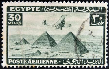 EGYPT - CIRCA 1946: stamp printed in Egypt shows plane over Pyramids at Giza, circa 1946