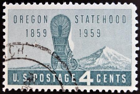 covered wagon: UNITED STATES OF AMERICA - CIRCA 1959: A Stamp printed in USA shows the covered Wagon and Mount Hood, Oregon Statehood Centenary, circa 1959