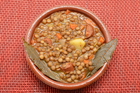 Brown lentil stew in bowl with vegetable photo