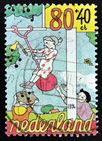 HOLLAND - CIRCA 1994: A stamp printed in The Netherlands dedicated to Child Welfare shows Helping to balance woman picking cherries, circa 1994 photo