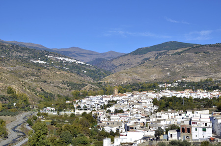 View of white village with the Sierra Nevada mountains to the rear, Cadiar, Las Alpujarras, Granada Province, Spain. photo