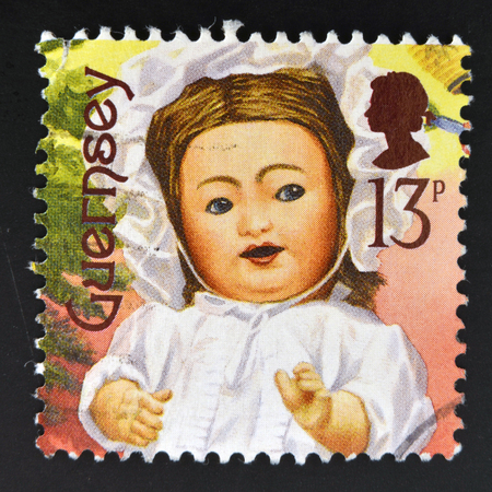 guernsey: GUERNSEY - CIRCA 1994: A stamp printed in Guernsey dedicated to bygone toys shows Doll Face, CIRCA 1994 Editorial