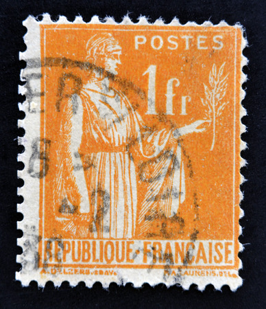 signifier: FRANCE - CIRCA 1932: A stamp printed in France shows a woman with an Olive Branch in hand - allegory of Peace, circa 1932