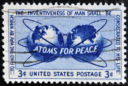 encircling: UNITED STATES OF AMERICA - CIRCA 1955: a stamp printed in USA shows Atomic Energy Encircling the Hemispheres, Atoms for Peace Policy, circa 1955