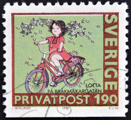 SWEDEN - CIRCA 1987: stamp printed in Sweden shows Girl on bike, circa 1987 photo