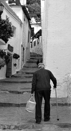 alpujarra: Elderly man climbs the stairs of a street in a town Stock Photo