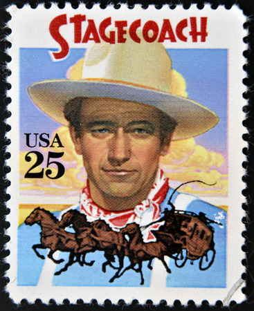 john wayne: UNITED STATES OF AMERICA - CIRCA 1990: A stamp printed in USA shows  portrait of American actor John Wayne as The Ringo Kid in Stagecoach Western film, circa 1990.