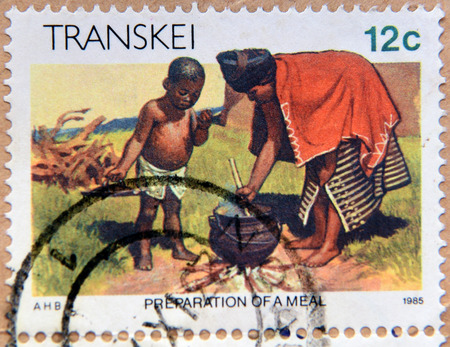 philatelist: REPUBLIC OF SOUTH AFRICA - CIRCA 1985: A stamp printed in Transkei shows woman preparation of a meal, circa 1985 Editorial