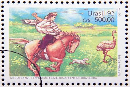 rhea: GRANADA, SPAIN - DECEMBER 1, 2015: stamp printed in Brazil dedicated to costume gauchos, shows a gaucho throwing ball at rhea, 1992