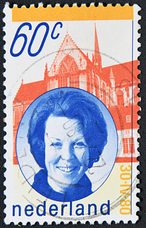 regnant: GRANADA, SPAIN - NOVIEMBRE 30, 2015: A stamp printed in Netherlands shows Queen Beatrix and New Church, Amsterdam, 1980.