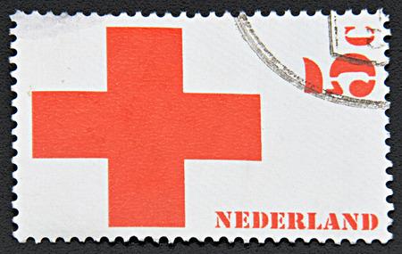 red cross: GRANADA, ESPA�A - 30 de noviembre, 2015: Un sello impreso en los Pa�ses Bajos muestra de la Cruz Roja