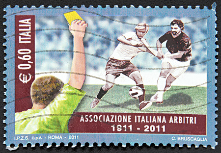 arbiter: GRANADA, SPAIN - NOVEMBER 30, 2015: A stamp printed in Rome shows men playing football and arbiter showing yellow card, 2011 Editorial