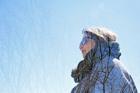 greem: Young woman with tree branch in autumn. Double exposure made with the camera. Stock Photo