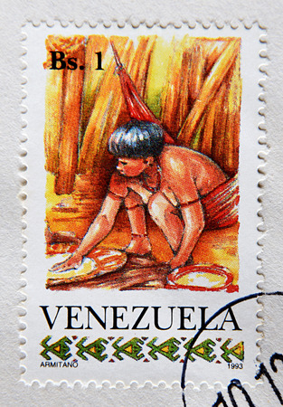 GRANADA, SPAIN - MAY 15, 2016: Stamp printed in Venezuela shows the Yanomami Woman Preparing Food, circa 1993 Editorial
