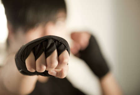 self defense: Detail of the Fist of a Male Kickboxer Throwing a Punch