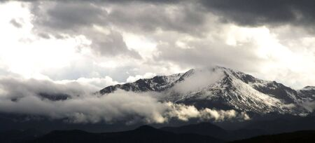 Its Pikes Peak, a snow covered mountain lit by the sun with a cloudscape, and surrounded by clouds at its bottom as well. Stock Photo