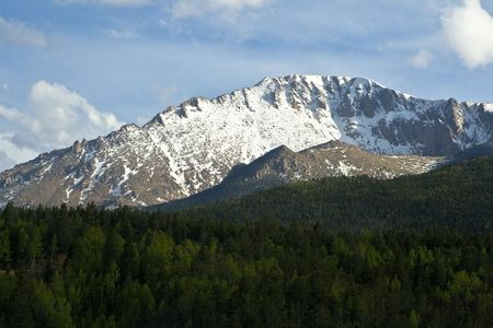It's Pike's Peak, a snow covered mountain in Colorado with a forest of trees in the foreground with a relatively cloudless sky.