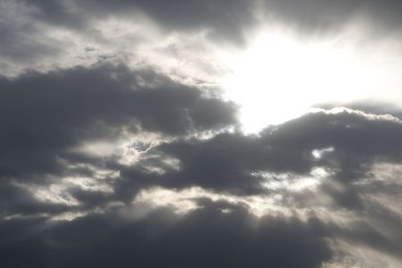 The sun is shining brightly from behind several clouds in the sky.