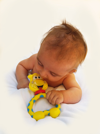 teething: 3 months old baby boy playing with teething toy