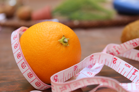 weight loss concept, orange and measuring tape
