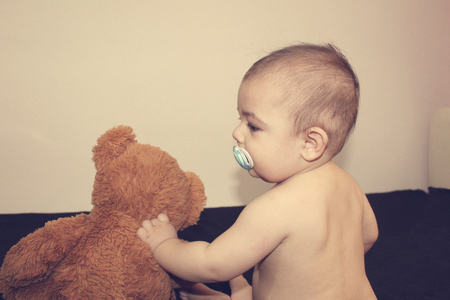 six months old naked baby boy huging teddy bear back view - best friends concept