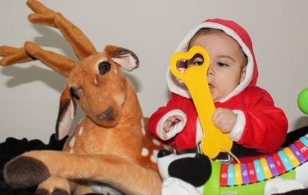 nine months old baby boy in santa clause suit with dear and toys ready for christmas