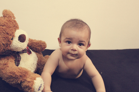 six months old naked baby boy huging teddy bear - best friends concept