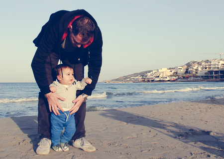 Daddy and baby boy on the sandy beach autumn, face expresion of happy family Banque d'images