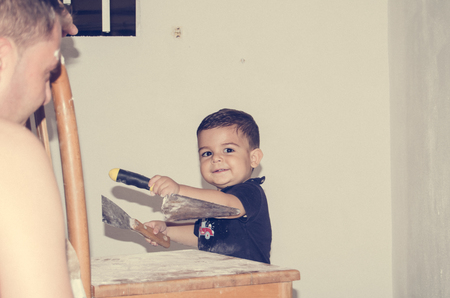 Father and one and half year old baby boy painting a room, little helper in the acction
