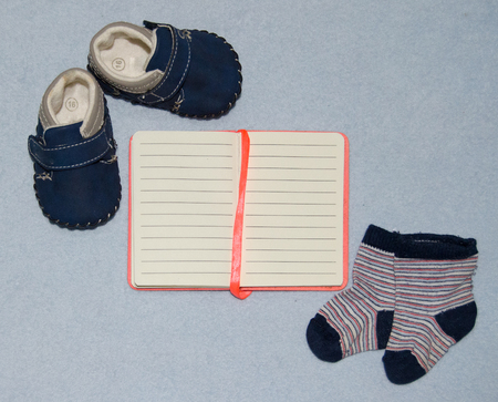 Table top view decoration baby shoes clothes notebook and toys. Flat lay, copy space Archivio Fotografico