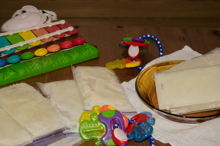 Frozen breast milk in storage bags in glass plate and on the wooden table, surrounded by teething toys and baby cow xylophone, mother milk ready to be stored in the freezer