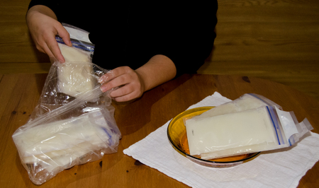 mother packing frozen breast milk in bag for further storage in freezer, woden table