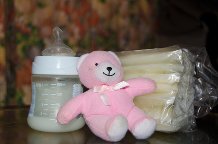 baby bottle with fresh expresed breast milk, frozen breastmilk in storage bags and soft toy pink teddy bear, breastfeeding concept