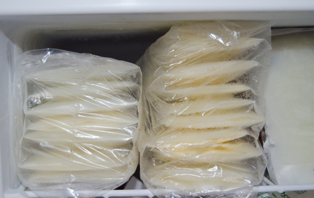 expresed breast milk packed in storage bags and frozen in the freezer, breastfeeding concept Banque d'images