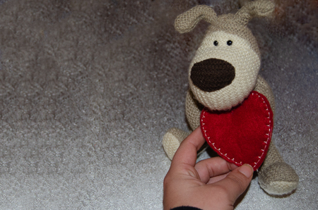 Gray hand made puppy soft toy with red heart - love concept, valentines day