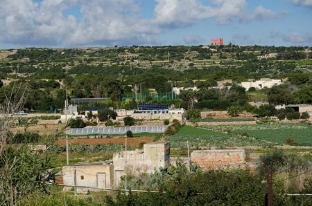 Mellieha, Malta - 30 december 2018 - Solar panels on the house in the middle of agriculture fields under Red tower - energy concept