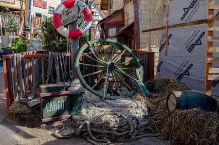 Mellieha, Malta, 30 december 2018 - Green coloured antique wooden wheel in popeye village or sweethaven village movie set