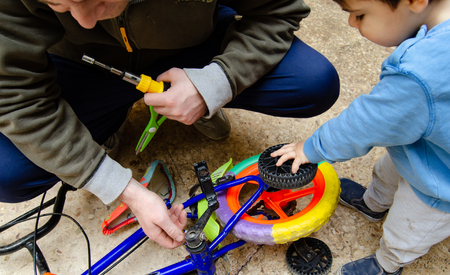 Father and two years old baby boy fixing old colorful rusty bike together. Reklamní fotografie