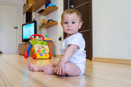 cute seven months old baby boy playing with educational toys on the floor
