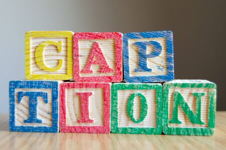 Educational toy cubes with letters organised to display word CAPTION - editing metadata and Search engine optimisation concept