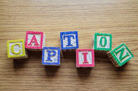 Cubes de jouets éducatifs avec des lettres organisées pour afficher le mot CAPTION - édition des métadonnées et concept d'optimisation des moteurs de recherche