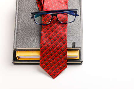 The concept of the teacher's day, School stationery with spectacles and tie on book