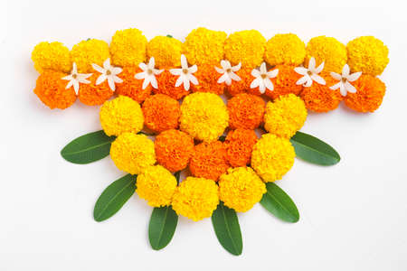 Flower Rangoli for Diwali Festival made using Marigold and leaf and Oil Lamp over white background,