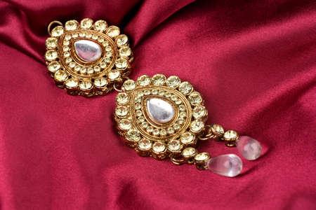 Kundan jewelry placed on red satin background. kundan and diamond pendant,Luxury female jewelry, Indian traditional jewellery, Bridal Gold wedding jewellery