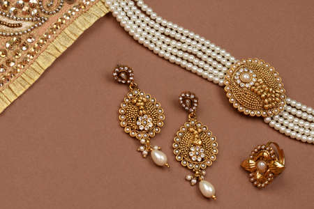 Pearl Jewelry on a brown background, Golden scarf, Pearl bracelet jewelry background, pearl necklace, pearl earrings, finger ring.Style, fashion and design of jewelry. indian traditional jewellery