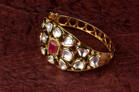 Gold bracelet on textured background,kundan bracelet,Style, fashion and design of jewelry. indian traditional jewellery,Indian wedding jewellery