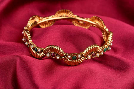 Indian golden Bangles. Bracelet with diamonds and stones on a red satin background, Indian Traditional Jewellery,Style, fashion and design of jewelry Standard-Bild